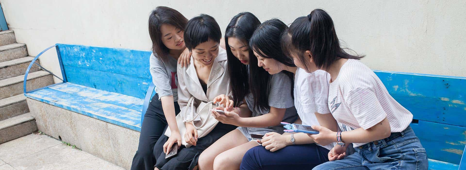 Five young Chinese women using social media